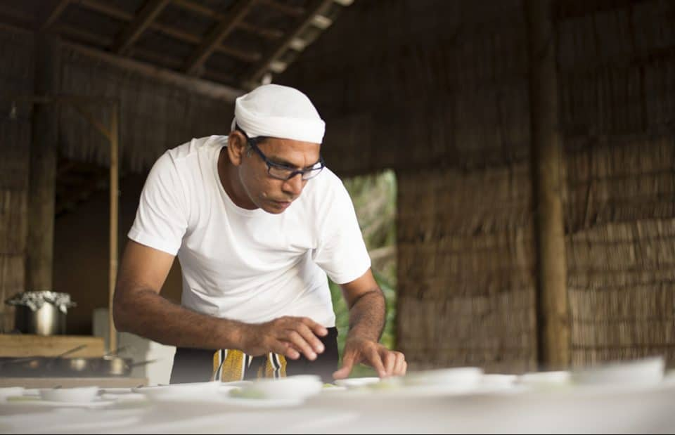 Chef de Cuisine at Soneva Fushi Abdulla Sobah preparing a dish in traditional Maldivian attire
